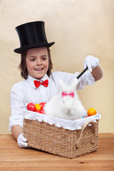 Happy magician boy conjuring an easter rabbit and colorful eggs