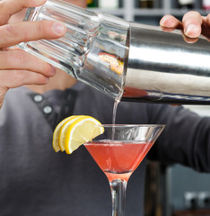 Barman's hands mixing cosmopolitan cocktail