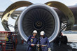 airplane mechanics in front of jumbo jet engine