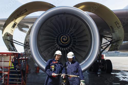 airplane mechanics in front of jumbo jet engine - 77790947