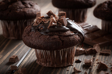 Chocolate muffins with icing and chocolate pieces
