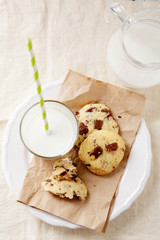 Fresh cookies on paper with glass of milk