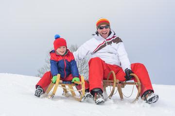 Vater und Sohn beim Schlittenfahren