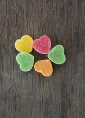 Candy in shape of hearts on wooden background. Top view.