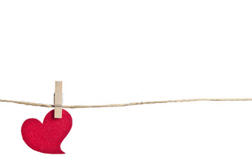 Red fabric heart hanging on the clothesline . On white backgroun