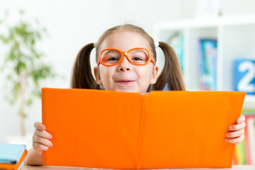 clever child little girl behind of open book indoor