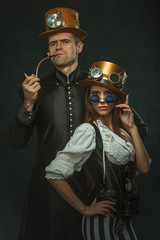 The couple steampunk. A man with a pipe and a girl with glasses