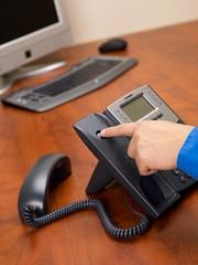 human hand disconnecting landline phone