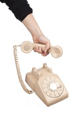 human hand holding receiver of rotary dial phone