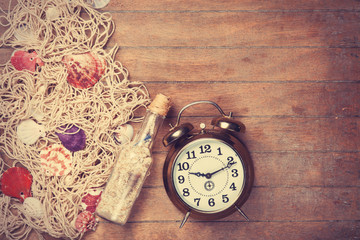Retro alarm clock and net with shells and bottle