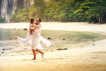 bride and groom whirl and kiss on sand beach