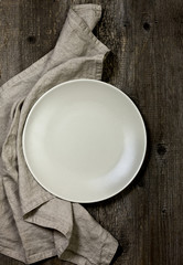 plate and linen napkins on wooden background in (dark)