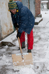 Man with snow shovel cleans outdoors in winter