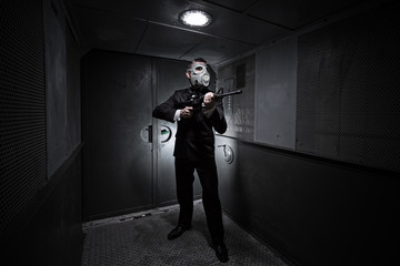 Male with the rifle and gas mask in an old elevator
