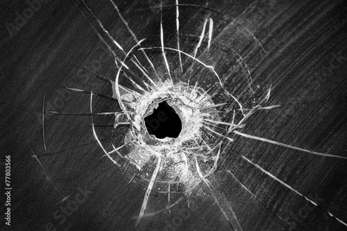 Leinwandbild Motiv Bullet shot cracked hole on broken window glass