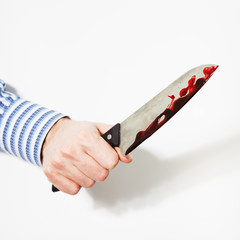 The hand  is holding the knife with blood