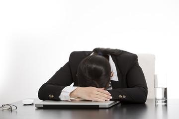 müden Geschäftsfrau mit ihrem Gesicht auf Tastatur des Laptops