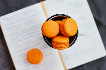 Orange macaroon upon open diary with notes