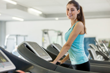 Young smiling brunette is running on a treadmill