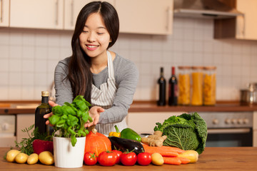 asian smiling woman standing in the kitchen with colorful ingred
