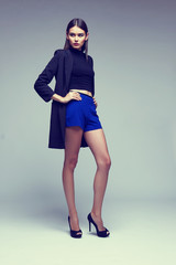 young elegant woman in blue shorts, black jacket. Fashion studio