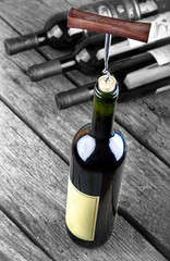 Wine bottle on a wooden table standing out from the crowd