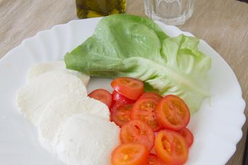 Piatto di mozzarella e pomodori con insalata