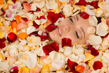 Beautiful sexy woman in bath with flowers petals
