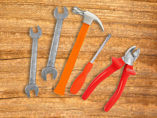 Hammer, screwdriver and wrenches over wooden background
