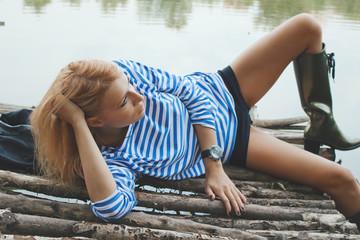 Beautiful blonde woman lying on old fishing bridge