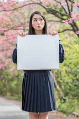桜をバックにホワイトボードを持つ女子学生