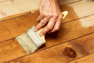 Man painting wooden floor