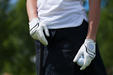 Golf player gloves hold the iron or putter