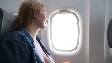 young beautiful girl looks out of airplane windo