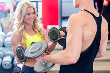 Couple with dumbbells at sport in fitness gym
