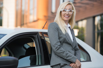 Mature businesswoman leaning on car outdoors