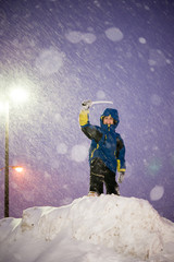 Happy Child Boy Playing During a Snowstorm