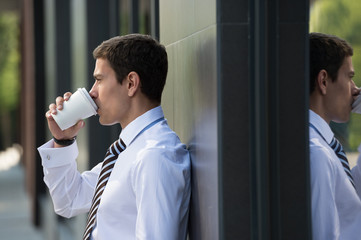 Businessman drinking coffee leaning on wall
