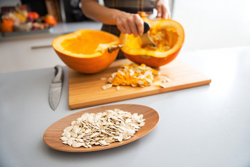 Closeup on seeds and housewife removing filling from pumpkin