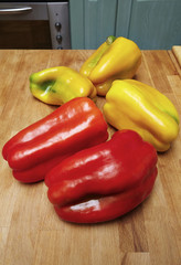 Italy, red and yellow sicilian peppers on a wooden kitchen table