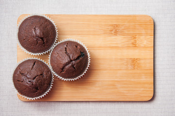 Chocolate muffins on the wood cutting board, text space