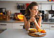 Young housewife eating pumpkin soup in kitchen - 77822320