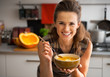 Leinwanddruck Bild - Happy young woman eating pumpkin soup in kitchen