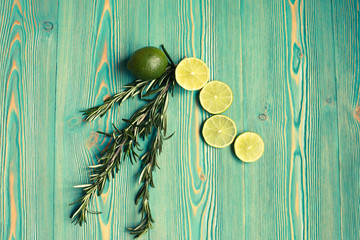 lime and rosemary on blue wooden table