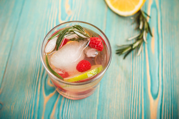 detox water with ice and fruits in glass, toned
