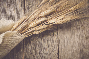 Wheat Ears over Rustic Wood and Burlap background