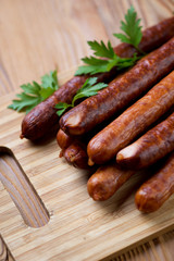 Close-up of smoked sausages on a wooden chopping board