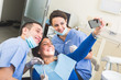 Dentist and Dental Assistant examining Patient teeth. - 77824103