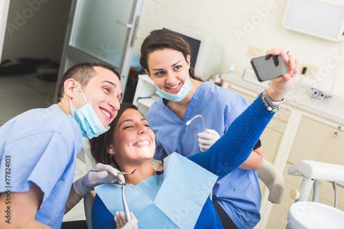 Leinwanddruck Bild Dentist and Dental Assistant examining Patient teeth.