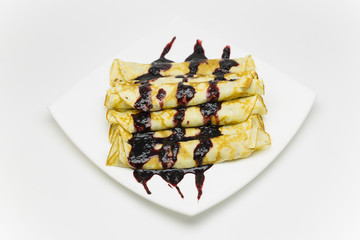 Russian pancakes of golden colour on a white plate watered with